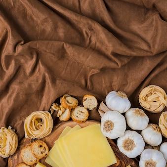 Formaggio a fette, pasta cruda, pane e aglio su stoffa marrone