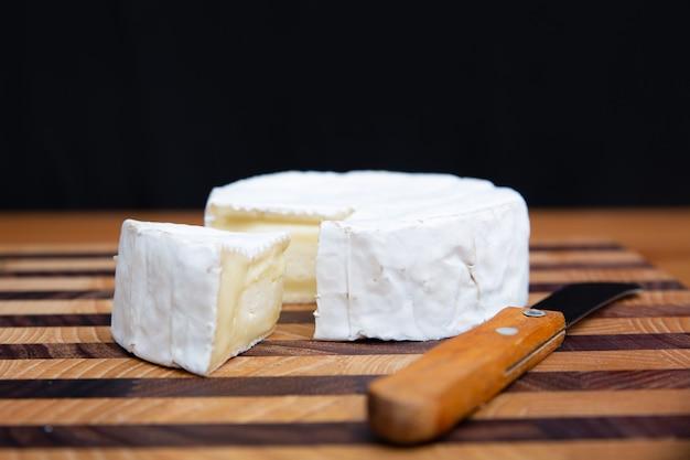 Formaggio a pasta molle e coltello che mettono su tavola di legno