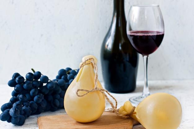Formaggio caciocavallo un bicchiere e una bottiglia di vino rosso, uva. formaggio pera