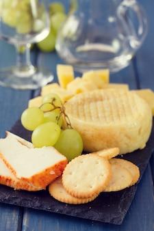 Formaggio con uva e biscotti e bicchiere di vino bianco