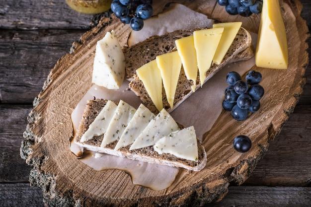 Formaggio con uva, pane, miele. formaggio di capra alle erbe aperitivo. bruschetta, formaggio