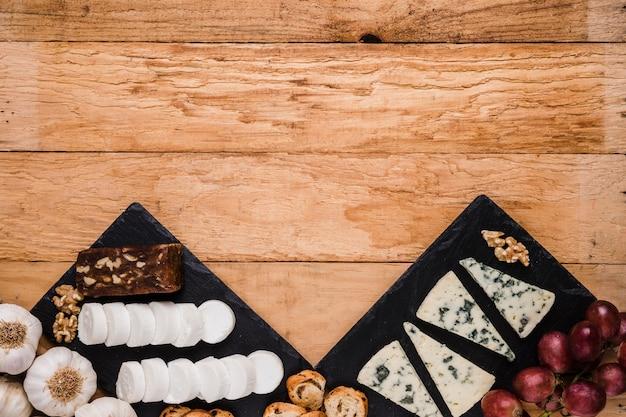 Formaggio di capra bianco e formaggio blu con ingredienti freschi disposti su superficie esposta all'aria