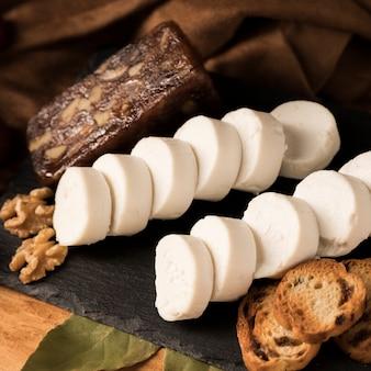 Formaggio di capra biologico, formaggio marrone, noci e pane con foglie di alloro su pietra ardesia
