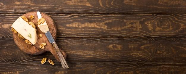 Formaggio di noci con formaggio e coltello speciale sul vecchio bordo di legno rotondo. concetto di cibo sano con spazio di copia, banner.