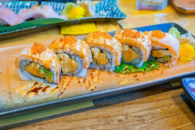 Formaggio di salmone, topping di california roll con formaggio e avocado, salsa di soia shoyu e uova di salmone giaceva sul piatto. rotolo di sushi di salmone, cibo giapponese. (punto di messa a fuoco selettiva)