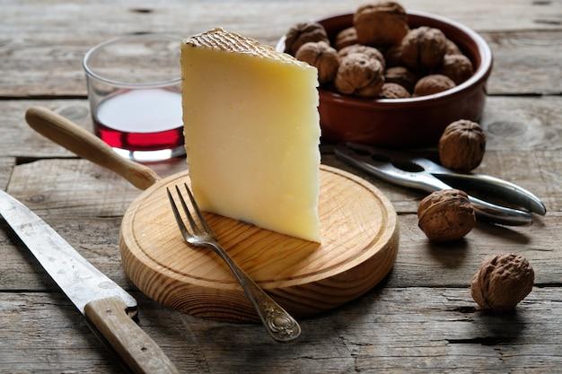 Formaggio e noci di manchego sulla tavola di legno rustica