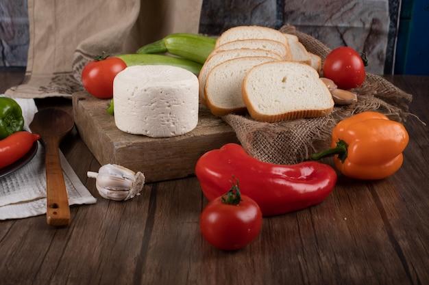 Formaggio e verdure su una tavola di legno