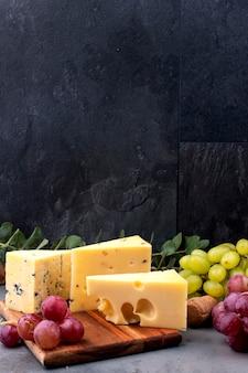 Formaggio ed uva assortiti su un bordo di legno e su un fondo concreto nero