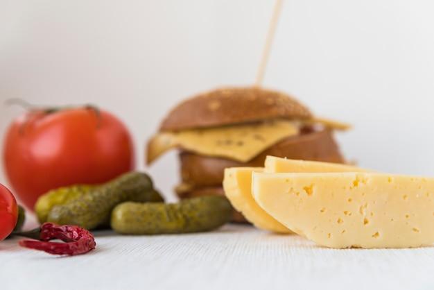 Formaggio fresco vicino a pomodori, cetrioli e sandwich