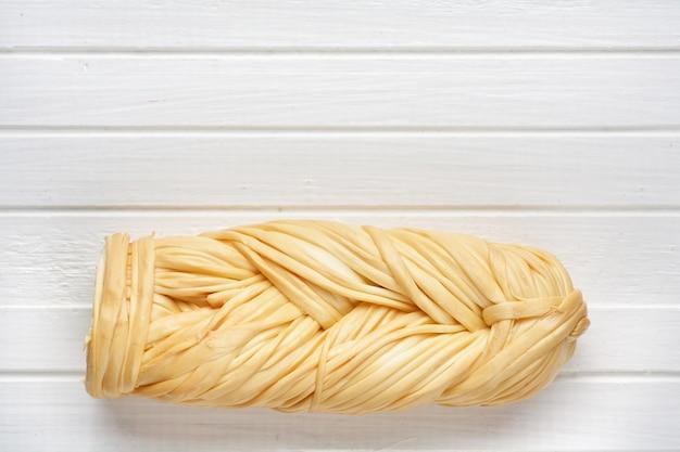 Formaggio intrecciato affumicato su un legno bianco