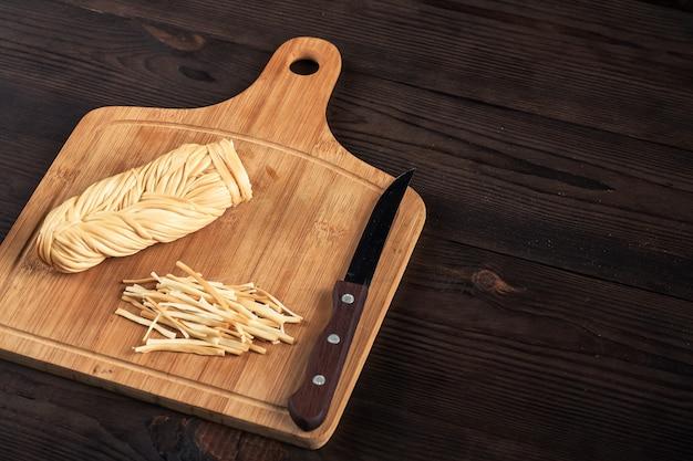 Formaggio intrecciato affumicato su un legno