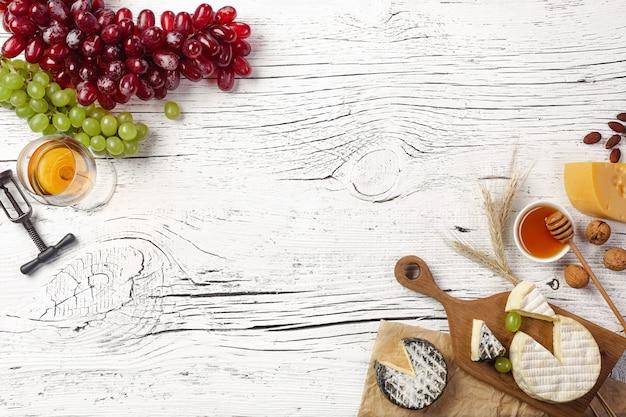 Formaggio, miele, uva, noci e bicchiere di vino sul bordo di legno bianco
