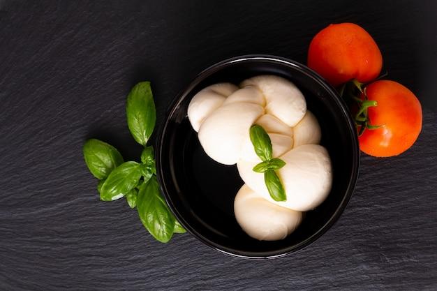 Formaggio mozzarella biologica in tazza di ceramica nera con pomodori e basilico con lo spazio della copia
