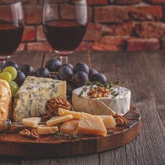 Formaggio, noci, uva e vino rosso su fondo in legno