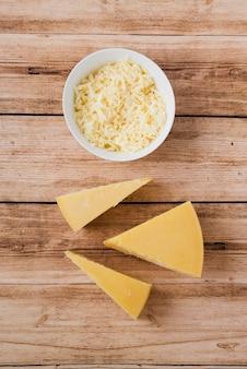 Formaggio pezzo di formaggio grattugiato e triangolare sul tavolo di legno