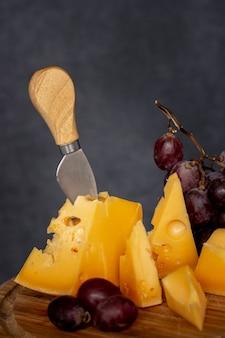 Formaggio saporito del primo piano con l'uva