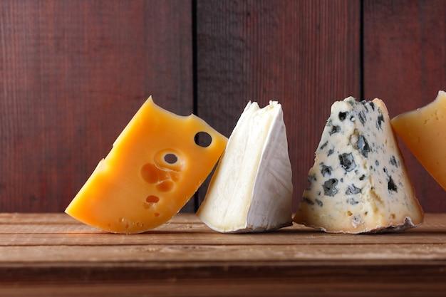 Formaggio su assi di legno. camembert, formaggio giallo duro, dorblu su assi di legno.