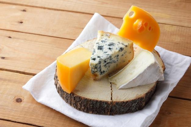 Formaggio su stoffa bianca. camembert, formaggio giallo duro, dorblu su assi di legno. prodotti lattiero-caseari sul tovagliolo bianco