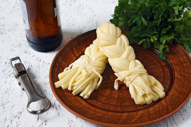 Formaggio su un piatto su un piatto grigio e birra. formaggio sulguni