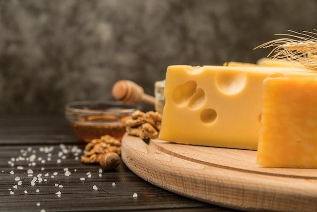 Formaggio svizzero saporito del primo piano sulla tavola con miele