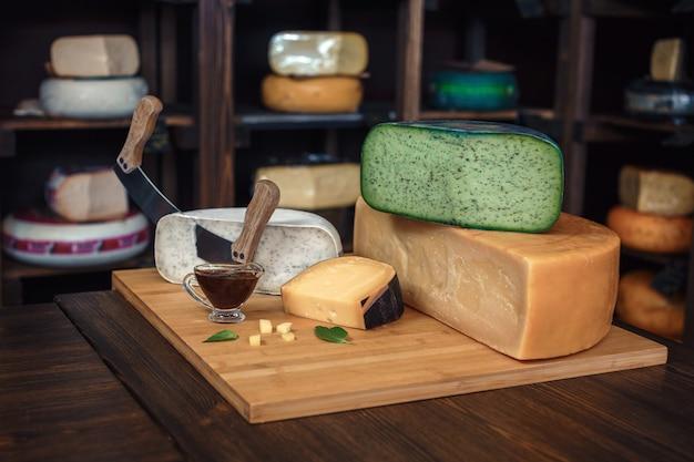 Formaggio teste con fette e coltelli su una tavola di legno con un interno