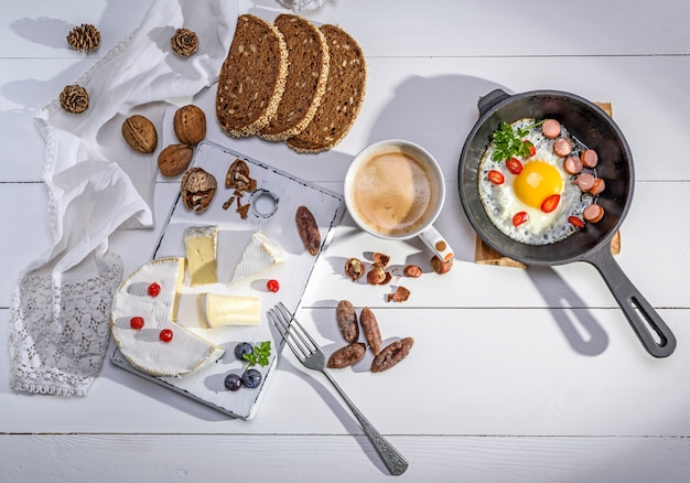Formaggio, una tazza di caffè e una padella nera in ghisa con un uovo fritto