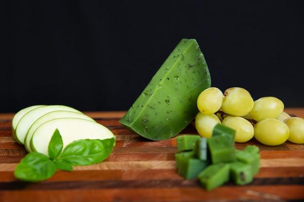 Formaggio verde, mela affettata ed uva che pongono sul bordo di legno