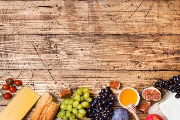 Formaggio, vino, fichi d'uva baguette miele e spuntini sul tavolo in legno rustico con copia spazio.