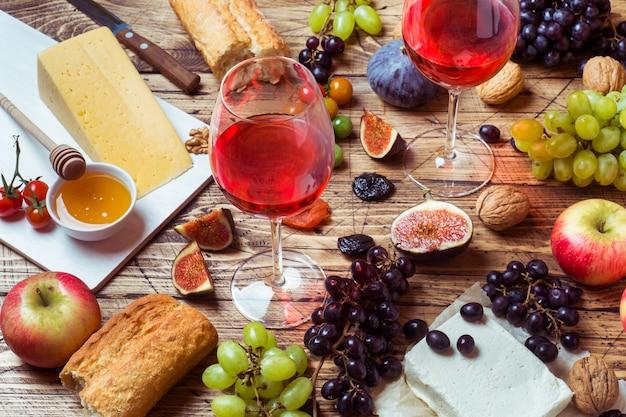 Formaggio, vino, uva di baguette, fichi miele e spuntini sul tavolo di legno rustico.
