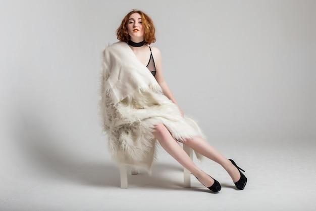 Formato curvy più donna modello capelli rossi in lingerie e giacca a sfondo bianco studio