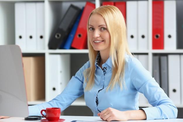 Formazione in ufficio donna d'affari. si siede alla sua scrivania guardando la telecamera e sorridendo.