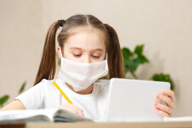 Formazione online a distanza. scolara che studia a casa con il taccuino del laptop della compressa digitale e che fa i compiti della scuola.