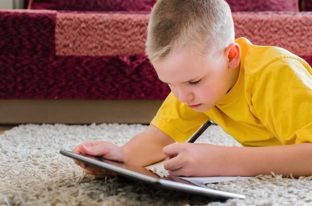Formazione online a distanza. scolaro che studia a casa con la compressa digitale.