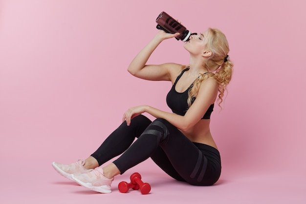 Formazione personale pubblicitaria. una giovane donna sportiva beve un frullato proteico da uno shaker dopo l'allenamento in casa. muro rosa