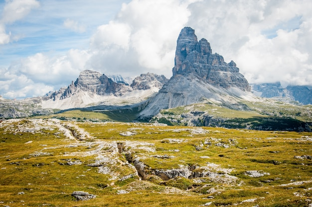 Formazione rocciosa sull'erba dell'ampio campo sotto cielo blu nuvoloso durante il giorno