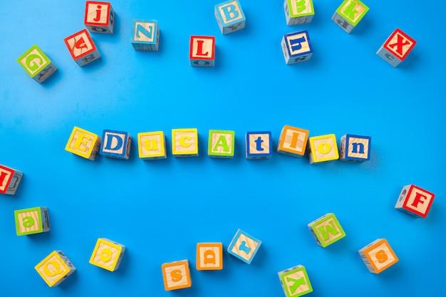 Formazione scolastica. blocchetti di alfabeto variopinto di legno su fondo blu, disposizione piana, vista superiore.