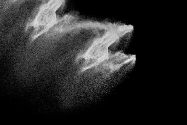 Forme bizzarre di nuvola di esplosione di polvere bianca su sfondo nero. spruzzata di particelle di polvere bianca.