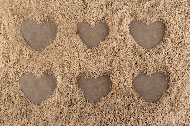 Forme di cuore su uno sfondo fatto di segatura