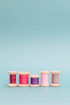 Forme diverse accontentano il concetto di personalità unicità. bobine di fili multicolori su un ricamo blu cucito cucito a mano vista dall'alto piatto disteso diverso diverso