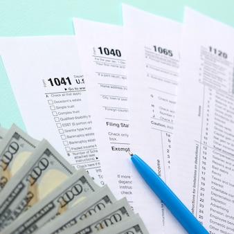 Forme fiscali si trova vicino a centinaia di banconote da un dollaro e penna blu