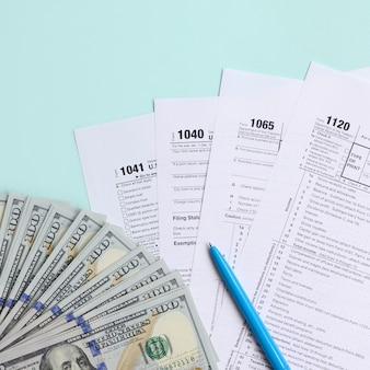 Forme fiscali si trova vicino a centinaia di banconote in dollari e penna blu su uno sfondo blu chiaro. dichiarazione dei redditi
