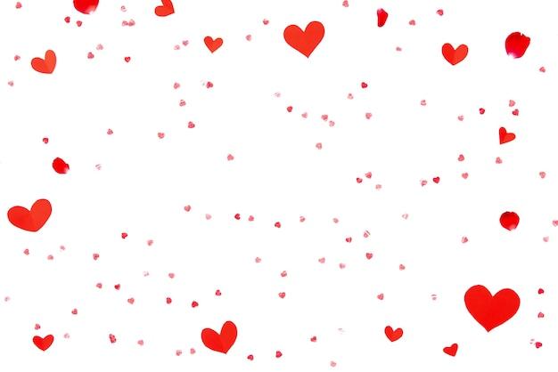 Forme rosse del cuore e petali di rosa sul fondo del libro bianco