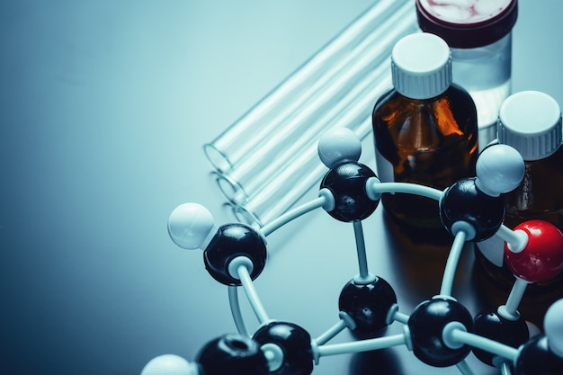 Formula molecolare e attrezzature di laboratorio su uno sfondo scuro con spazio di copia.