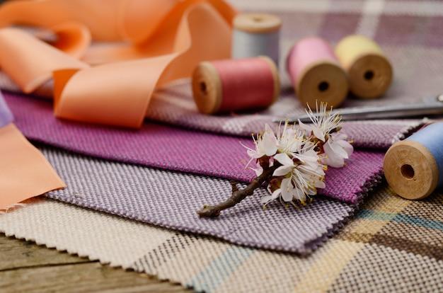 Forniture per cucire, aghi, forbici sul colorato tessuto di iuta