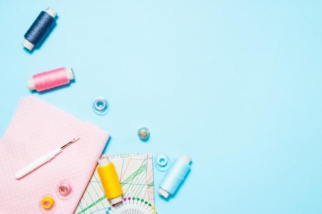 Forniture per cucire, modello e accessori per il ricamo su sfondo blu, cuciture, ricami. spazio per il testo. vista piana, vista dall'alto.