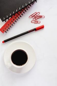 Forniture per ufficio con quaderno a spirale, penna, graffette e tazza di caffè nero