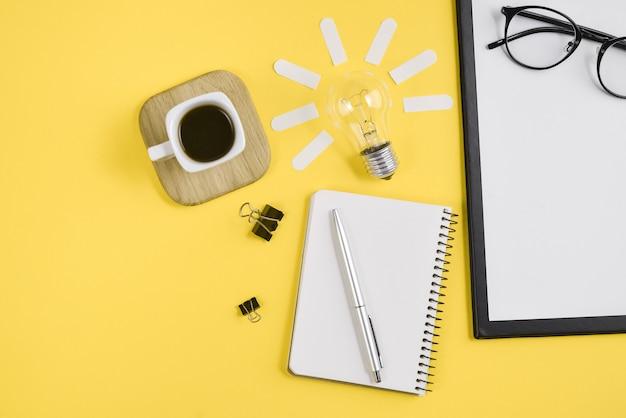 Forniture per ufficio design in stile ufficio con penna, blocco note, occhiali, tazza di caffè e lampadina