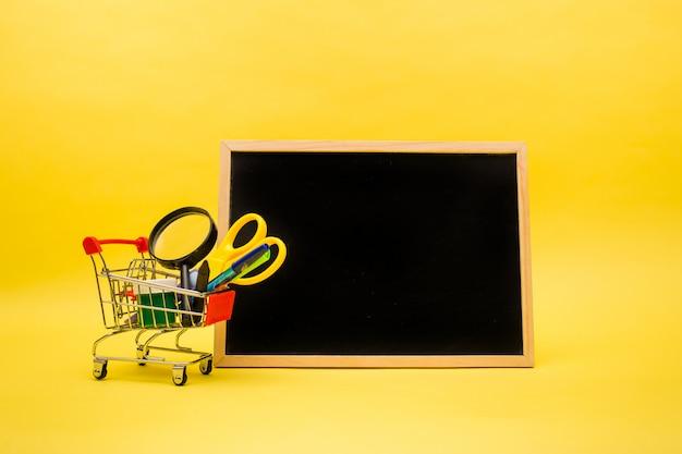 Forniture per ufficio in un carrello di metallo e un'ardesia vuota su un giallo isolato con una copia dello spazio