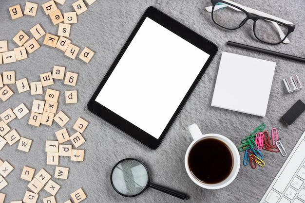 Forniture per ufficio; lettera scatola di legno e tavoletta digitale su sfondo grigio