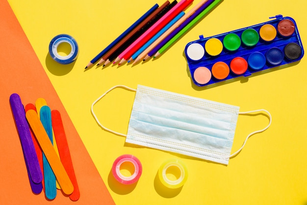Forniture scolastiche accanto a una maschera per il viso, sfondo piatto laici torna a scuola.